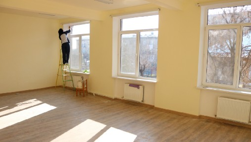 woman putting the finishing touches on a newly renovated room at a school