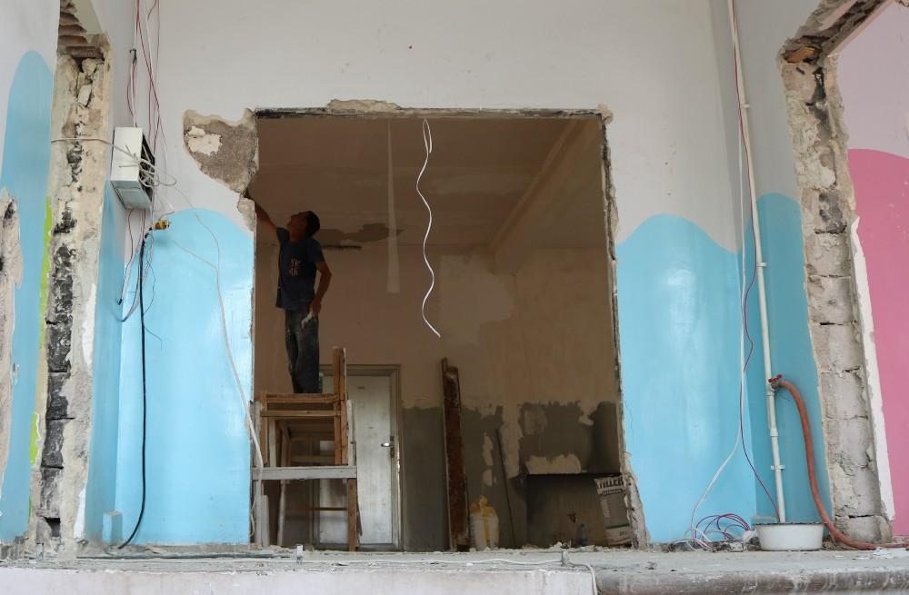 A man renovating a room in a school